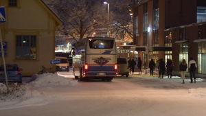 En buss kör iväg från busstation. Man ser bara baklyktorna. Vinterlandskap. Några ungdomar som stigit av bussen går på trottoaren.