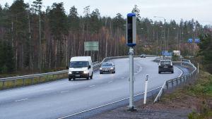 En avlång smal trafikkamera intill en asfalterad väg med några bilar på.