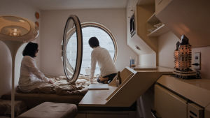 Ett ultramodernt hotellrum där en man och kvinna sitter på sängen och ser ut genom ett runt fönster.