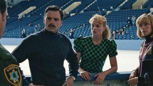 Tonya, maken Jeff och tränaren Diane blir förhörda av en poliskonstapel vid rinken.