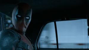 Deadpool tittar rakt in i kameran genom bilfönstret.