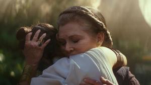 Rey (Daisy Ridley) och Leia (Carrie Fisher) omfamnar varandra i solskenet.