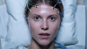 Thelma (Eili Harboe) makaa sairaalasängyllä katsoen kameraan johtoja päässään.