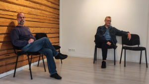 Två män sitter på var sin stol i ett rum med en vit vägg och en stockvägg.