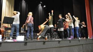 Flera kvinnor på en scen. De värmer upp och står därför i olika ställningar.