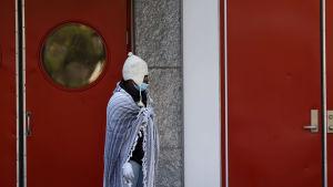 En man har svept in sig i en filt för att skydda sig mot kylan