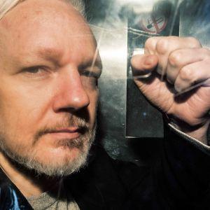 Julian Assange gestikulerar till pressfotografer under en fångtransport till en domstol i London den första maj 2019.