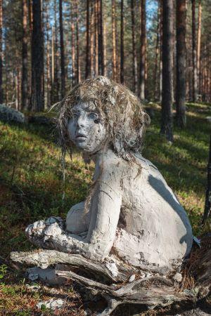 Lapsenmuotoinen vaaleasta massasta muotoiltu patsas, hiukset sammalta, katsoo kuvasta vasemmalle, taustalla metsää