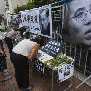 Människor i Hongkong lämnar sina kondoleanser efter Liu Xiaobos död. Ett foto på änkan Liu Xia i förgrunden. 14.7.2017.