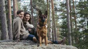 Mun luonto -viihdeshown juontajat Kimmo Ohtonen ja Viivi Pumpanen istuvat sammaleisella kalliolla. Kuvassa myös Viivin saksanpaimenkoira.