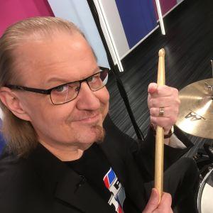 Koomikko Jope Ruonansuu rumpusetin takana Puoli seiskan studiossa
