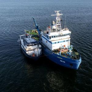 Flygfoto av de två blåa forskningsfartygen Electra af Askö och EVA-316 taget den 11 juni 2021 under den tredje dagen av den svensk-estniska dykoperationen vid MS Estonias vrak i Finska viken.