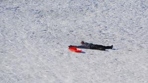 En kvinna ligger på rygg brevid en pulka i pulkabacken vid borgbacken i Borgå