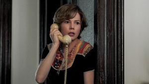 Gail (Michelle Williams) står i dörröppningen med en telefonlur i handen och ser skrämd ut.