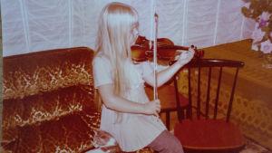 Gulnat foto av Raakel som övar violin sittandes på soffkanten som liten.