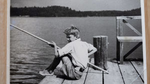 Svartvitt foto av Caj Bremer som barn som sitter och metar på en brygga.