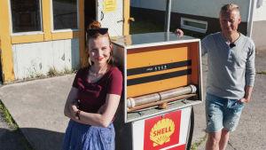 Man och kvinna lutar sig mot gammal bensinpump. I bakgrunden en liten kiosk med gula knutar samt texten SHELL.