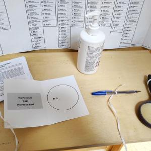Ett röstningsbås med en valsedel, handspritsflaska, förstoringsglas och fastbunda pennor.