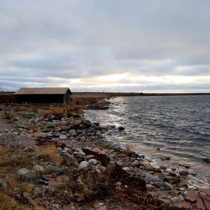ett uthus vid en stenig strand i solnedgång med vågor i havet