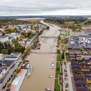 Flygbild över en å som flyter genom höstlig stad
