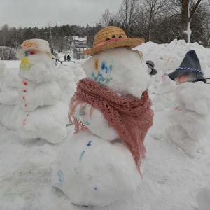 En glad snögubbe med stråhatt och rosa halsduk står bland flera andra snögubbar.