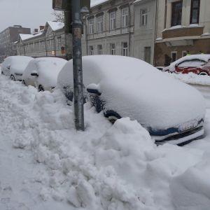 Tre bilar är helt insnöade längs en gata som plogats. Det har snöat 30 centimeter under natten.