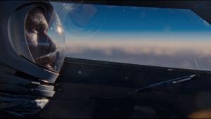 Neil Armstrong i sitt plan med himlen utanför.