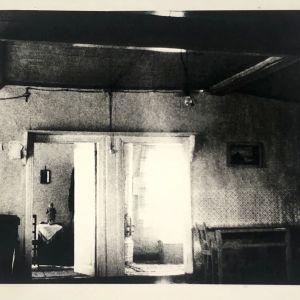 Pohjalainen tupanäkymä, jossa kaksi kamarin avointa ovea ja toisessa kamarissa nukke pöydällä.