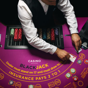 En croupier vid ett blackjackbord.