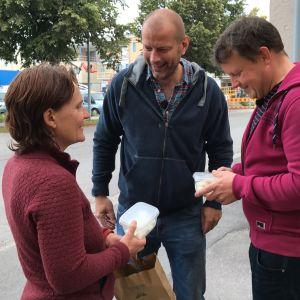 Shanti Paz Limnell står med en låda fetaost i handen invid Matias Jungar och Michael Björklund.