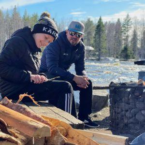 Roope Rajala ja Janne Nissinen istuvat nuotiolla Koitelinkoskella