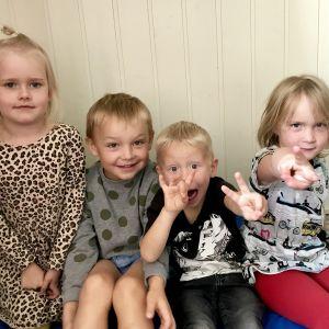 Fyra barn i dagisåldern sitter bredvid varandra på en madrass.
