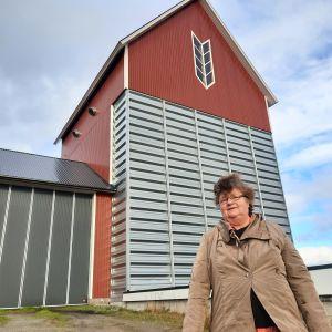 en kvinna med brun rock står framför en stor lagerbyggnad