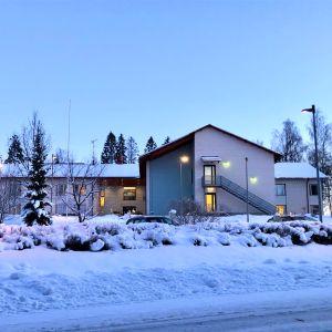 Ett tvåvåningshus i skymningstimmen, vinter, stort hus, det är ett äldreboende. Snö, gatulyktor.