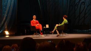Två personer sitter på en scen och samtalar