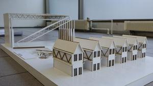 Miniatyrmodell med sex radhus i förgrunden och en halvt nedmonterad lagerhall i bakgrunden.