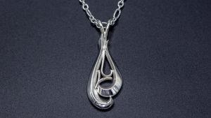 Ett halsband i silver format som en vattendroppe som utgörs av flera avlänga bitar ligger på en mörkblå botten.