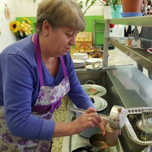 En person häller upp kakao i ett soppkök.