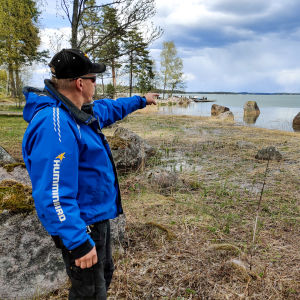 En man i blå jacka står på en strand och pekar ut på vattnet.