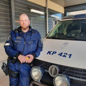 En uniformklädd polis står framför en stor polisbil