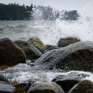 Havet stormar, vattnet slår mot klippor vid en strand.