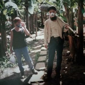 Ylen kuvausryhmä banaanipellolla maskit naamalla.