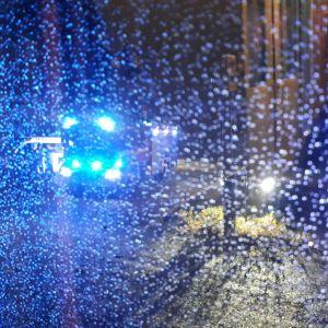 Brandbil med blåljus på som syns genom fönster med vattendroppar.