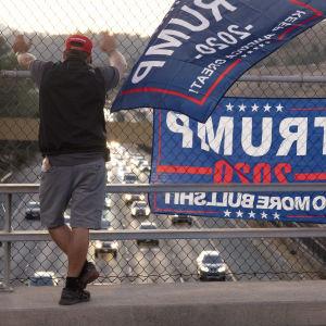 En Trump-supporter står vid en motorvägsöverfart och ser ut över vägen. Han har Trump-plakat bredvid sig.
