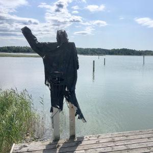 en svart figur gjord av tyg och trä vinkar ut mot havet.