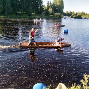 Två män åker i en öykstock eller ekstock längs med en å.
