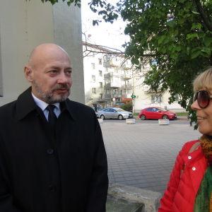 En skallig man i svart rock och en kvinna i röd rock med duk på huvudet står på en gata.