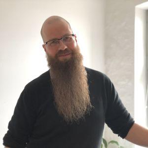 Porträtt av en man med långt skägg och mörk tröja.
