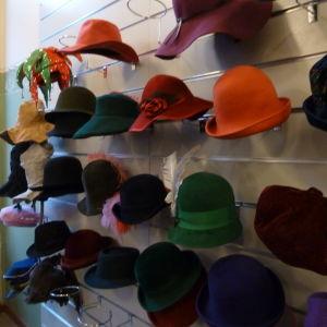 Färggranna damhattar på en ställning i hattaffären.