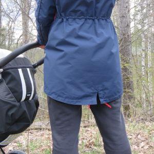 Ryggen av en kvinna  som håller i en barnvagn.